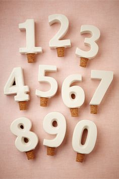 Numbered bottle stoppers as table numbers--love this idea!