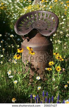 Old tractor seat on top of an old milk pail, in the midst of flowers. <3