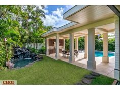 Covered patio with outdoor kitchen, pond, and pool of luxury home in Honolulu, Hawaii