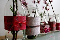 The simplicity of these Mason Jar vases is what makes them so captivating. They are wrapped in fabric (wrapping paper, maybe) and tied with ribbon. Then, 2-3 long stemmed flowers are placed inside each jar.