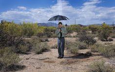 Hombre en desierto con el paraguas mojándome