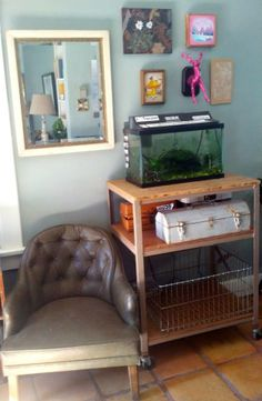 mini art gallery with fish tank lighting also seating nook by window. craft supplies on roller cart.
