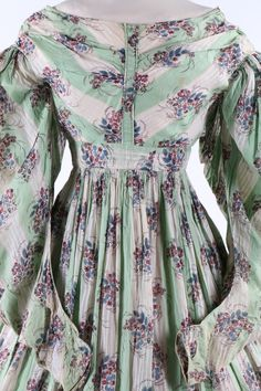 A printed cotton and muslin day dress, circa 1835. in peppermint green and white stripes with floral roundels.  Kerry Taylor Auctions.