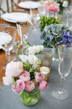 White lisianthus and soft pink ranunculi pop against the soft gray table runner.