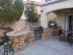 Outdoor kitchen with counter top firepits and pizza oven.