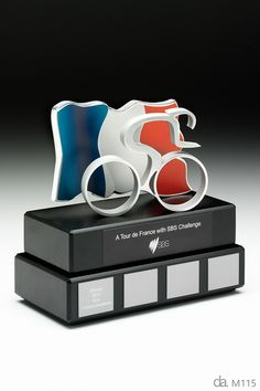 SBS: A Tour de France with SBS Challenge Custom made Perpetual Trophy. Custom metal , piano black base. Photographic aluminium flag. H: 250mm W: 200mm.