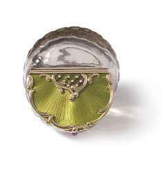 naturalistically carved from smokey quartz into the form of a shell, the undulating hinged gold lid edged with chased gold rocaille and enamelled translucent chartreuse green over a sunburst guillochage emanating from a trellis set with rose diamonds at its interstices, the thumb piece set with a cabochon ruby flanked by old brilliant cut diamonds. Moscow, pre 1896, 56 zolotniks. 5.7 cm by 4.8 cm by 3.5 cm