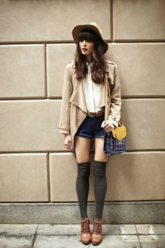 Shop this look for $188:  http://lookastic.com/women/looks/hat-and-trenchcoat-and-button-down-shirt-and-knee-high-socks-and-belt-and-shorts-and-boots/1834  — Khaki Hat  — Tan Trenchcoat  — White Silk Button Down Shirt  — Charcoal Knee High Socks  — Brown Leather Belt  — Navy Denim Shorts  — Brown Leather Boots