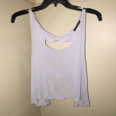 Brandy Melville Light Blue Tank Cute, cropped tank. Light blue color with a cute bow design on the back. Small hole as shown in the photo. NO TRADES Brandy Melville Tops Tank Tops