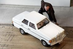"""An employee poses with a Mercedes-shaped coffin from Ghana at the exhibition """"Boxed: Fabulous Coffins from UK and Ghana"""" at the Southbank Centre in London January 19, 2012. REUTERS/Stefan Wermuth"""