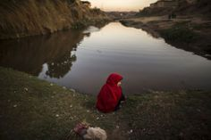 A girl sits on the edge of a stream in a slum on the outskirts of Islamabad (Pakistan).