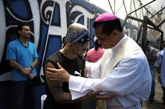 San Salvador, El Salvador: Catholic priest Fabio Colindres speaks with a member of Mara Salvatrucha gang during a mass at the prison in Ciudad Barrios