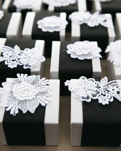 Favor boxes wrapped in black grosgrain ribbon and topped with lace flower appliques