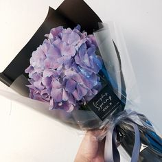 Wrap a single hydrangea with colored paper and clear cellophane.