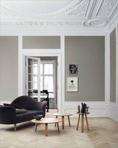Det lille som er av møblering er plassert midt i rommet, det understreker stuens storhet. Sofa, bord og lampe fra Gubi. Ønsker du å male veggen i en tilsvarende gråfarge, gå for Industriell Grå fra Jotun eller Cape Town fra Fargerike.