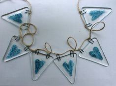 This fused glass bunting has been handmade by myself and fired to 800 degrees in my kiln then slowly cooled to ensure strength.  The bunting pieces measure approximately 7 cm by 6 cm and are stung on string at 10 cm intervals. There are 6 bunting tiles in total each with single blue heart fused in bubbles into the glass.  These make lovely gifts and are great decorations for parties and weddings.