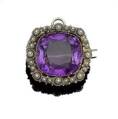 An amethyst brooch/pendant, circa 1830 The large cushion-shaped amethyst, within a border of cannetille decoration, width 3.1cm