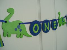 Este primer cumpleaños alegres dinosaurios de madera cuenta con 2 que se han pintado a mano en verde lima y azul de la bandera, y cada dinosaurio mide aproximadamente 5 1/2 de largo y 4 de ancho. En el centro de esta bandera son cartas de cartulina verde de cal que decir «Uno» y se unen