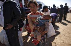 Rula, un niño de ocho años de edad, niña refugiado kurdo sirio sostiene su hija de tres meses de edad, hermano Ciwan, espera para el transporte después de cruzar hacia Turquía, cerca de la ciudad turca del sudeste de la provincia de Sanliurfa Suruc 1 de octubre de 2014 (Foto: Murad Sezer / Reuters)