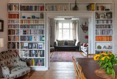 wall of bookshelves in dining room, with reading chair, frames entry to living area in English Victorian