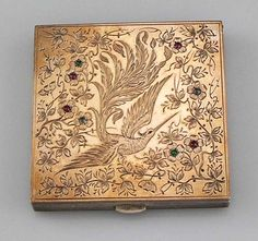 """Interesting Continental Compact    An unusual sterling Austrian silver compact with an engraved gold panel set with small cabochon rubies, sapphires and emeralds. Fine hinge craftsmanship. A large bird engraved in the center of the gold panel. Length: 2 3/4"""" square.    Price: $375.00"""