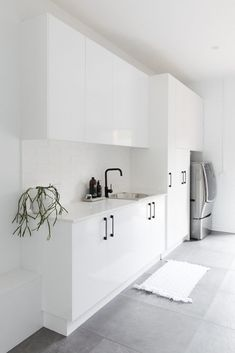Large and contemporary white laundry with grey floor tile. Modern and streamlined laundry with black handles and accessories. White Laundry Rooms, Modern Laundry Rooms, Laundry In Bathroom, Laundry Nook, Garage Laundry, Laundry Decor, Laundry Room Inspiration, Grey Bathrooms, Grey Floor Tiles Bathroom