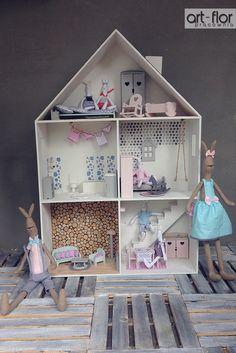 Domek dla lalek - ściana wyłożona plasterkami drewna.
