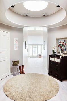 Edellisestä kodista tuotu pyöreä matto sopii täydellisesti samanmuotoiseen aulaan. Kartellin kevyt jakkara on hyvä istuinpaikka perheen kuopusta puettaessa. Ikean lipasto maalattiin ja siihen vaihdettiin vetimet. Anna Snellmanin kukkamaalaus periytyy Vilhelmiinan lapsuudenkodista, pikkutaulut on hankittu Society6.com:ista. Koristenorsu on Kupittaan Saven. Eteisen seinät on maalattu Tikkurilan sävyllä X481.