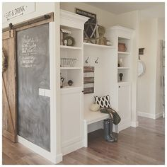 entry, chalkboard wall, hook and bench cubby in entry, barn door, white wood black via yellowprairieinteriors