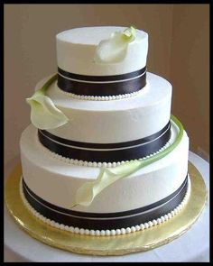 i like the double ribbon effect, though different flowers and colored ribbon. possibly a few tiny pearls coming up from the ribbon along with the change of shape to square? you can tell i work where they make wedding cakes!