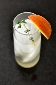 Peach sangria made by infusing a sweet moscato wine with fresh-cut peaches and fresh thyme