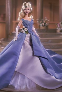 Grand Entrance™ Barbie® doll wears a steel blue taffeta gown with a fitted bodice and long, full skirt with an underskirt of blush pink satin and ivory/pale pink tulle. Beautiful blush roses at her waist, and long blush gloves accent this classic look. The finishing touches include blush pumps, and rhinestone and faux pearl earrings.