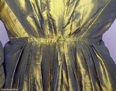 Changeante silk gown, 1815-25, green and gold silk taffeta, square neckline, very high narrow inset waistband, tubular long sleeves, small train, sleeves probably altered from an earlier style. Augusta Auctions