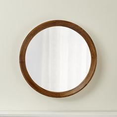 Deceptively simple, the Anurhada round wall mirror is the result of skilled artisans who piece together precise shapes of mango wood into a ring, which is then turned to complete its round shape and achieve its graceful inverse bevel. A brown stain brings out the wood's rich color and grain. A modern classic, the round mirror's clean look complements any décor.