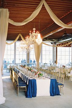 Dazzling wedding reception decor with crystal chandeliers, long tables covered in ocean blue linens, garland chair decor and centerpiece florals in pink, peach, ivory and green. Design by Shindig Weddings & Events, florals by Southern Blooms by Pat's Floral Designs, chandeliers by Blue Ridge A/V and Lighting, image by Adam Barnes Photography.