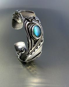 Tis piece is fine silver metal clay over top of a sterling silver core.  I set a Labradorite cab as a focal piece. --Lisa Barth