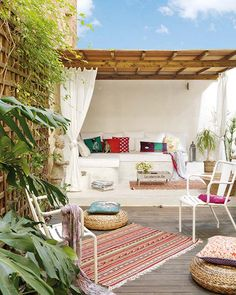 Bohemian entertaining corner - bright boho cushions, timber deck, woven floor pillows, fresh white walls & lounge...