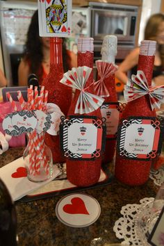 Queen of Hearts themed party - DIY red glitter champagne bottles and red/white straws.