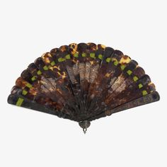 Brisé fan of tortoise shell with green silk ribbon. Blades mostly plain with three carved panels. Guards carved in high relief.