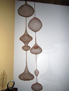 hanging copper sculpture 8ft.  Inspired by the wondrous work of Ruth Asawa........my hanging sculptures are handmade from a single strand of fine copper wire. These pieces are very light weight and hang from the ceiling. They cast beautiful shadows in the evening hours when illuminated.