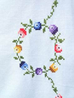 A white vintage square embroidered cross stitch tablecloth with pretty small colorful flowers. This tablecloth is made from white cotton material and has embroidered flowers in pink, purple, blue, orange, and yellow. It is in very good conditin, no stains or flows. Freshly washed and