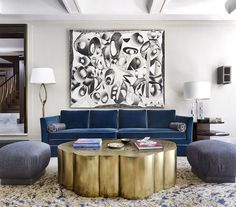 In the living room, a painting by Barry Reigate hangs above a custom sofa covered in blue velvet; the cocktail table is by Erwan Boullud and the floor lamp is vintage Felix Agostini.