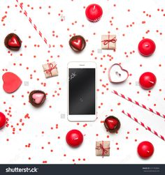 Styled Valentines Day flatlay top view. Smartphone, sweets, presents, candles, box with proposal ring  and confetti on white. Holiday concept. Copy space for text