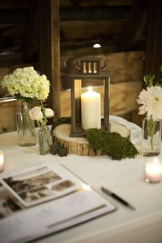 Rustic New York Real Wedding | Confetti Daydreams - Guest sign-in book displayed on a table decorated with tealight candles, old bottles filled with flowers and a candle in a wooden lantern box set upon a tree stump ♥ #Wedding #RusticWedding #Rustic #BarnWedding