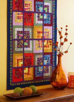 Sew Scrappy-To make a graphic quilt, pieces six Log Cabin blocks, cut them in fourths, and sew them back together again set off by purple sashing. The finished result creates a windowpane effect.