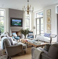 Love the sofa and color, wall art, chandelier and tv over simple fireplace.