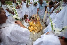 Brasilia, Brazil: a girl dressed in ceremonial Oxun clothing is surrounded by members of the African-Brazilian religion of Candoble during a washing ceremony using lavender water as part of events commemorating National Black Consciousness Day