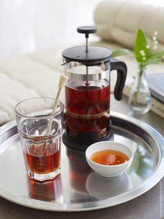 Eftermiddagsteét serveras på GROGGY bricka. UPPHETTA kaffe-/tepress, POKAL glas, liten IKEA 365+ skål. Vas i bakgrunden VÅRVIND.