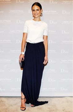 Jordana Brewster wears a white t-shirt tucked into a navy blue maxi skirt, black heeled sandals, a clutch, and statement jewelry