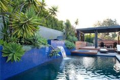 This stunning pool area features vibrant blue tiles, a waterfall and hot tub. A black pergola is positioned over a teak deck and black Adirondack chairs, while tropical plants line a gray stone wall.